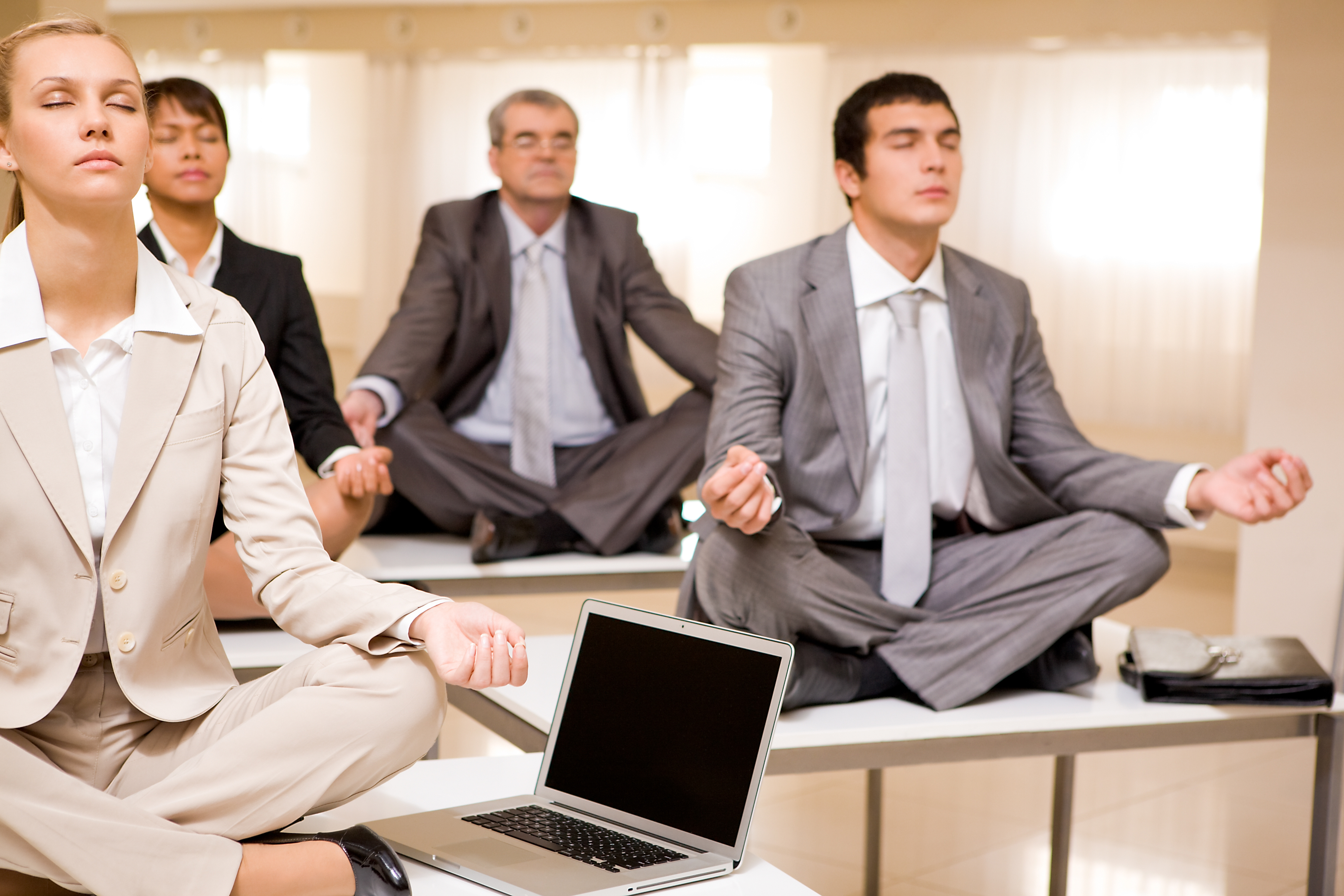 Portrait of meditating business people sitting on desks with their legs crossed in office
