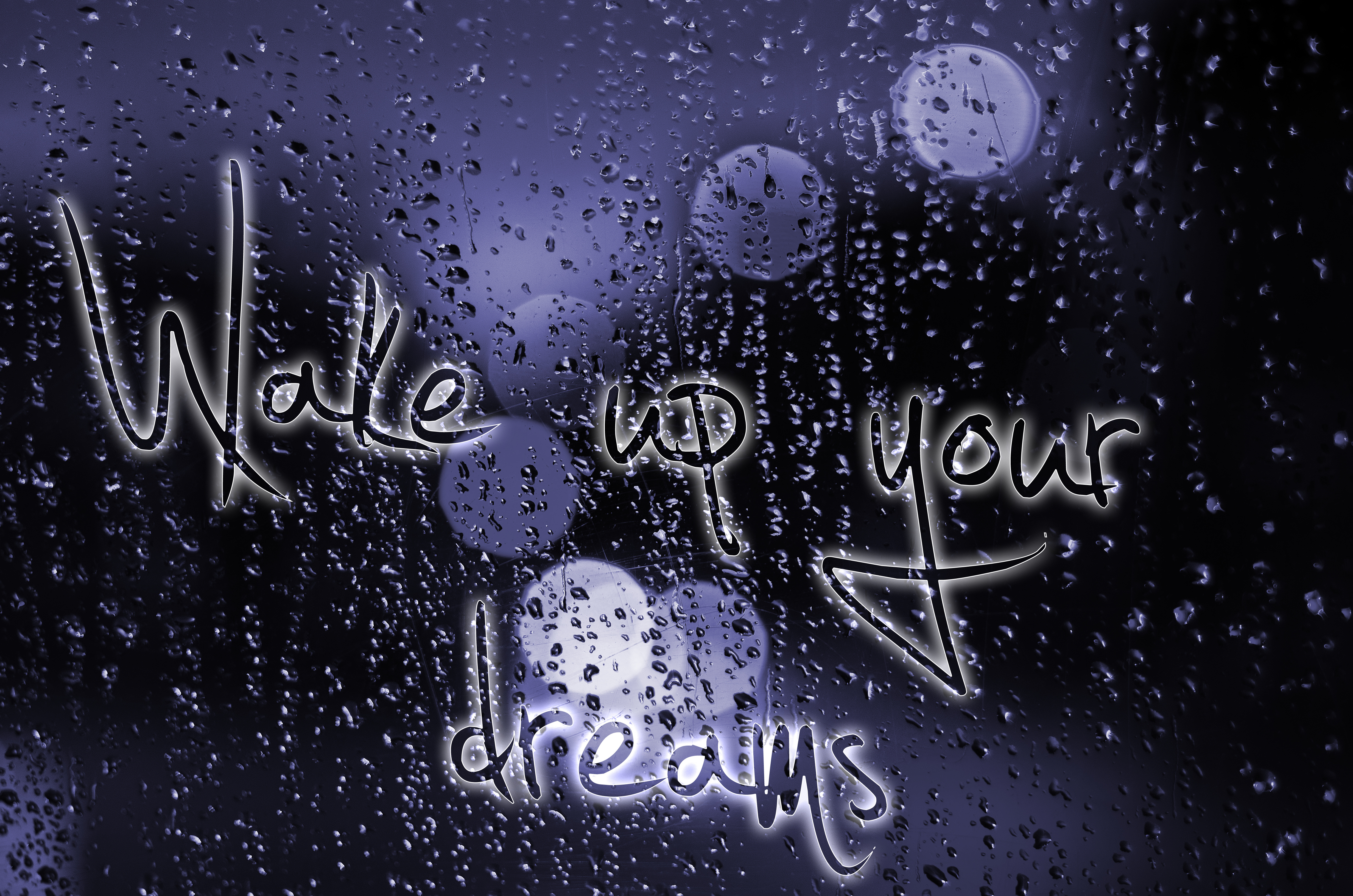 Sentence Wake up your dreams written on a wet glass. Night city life through windscreen: darkness and rain.
